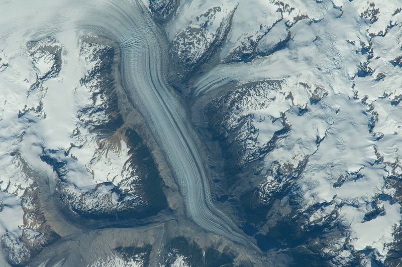 Caption by Space Station Academy student: This image appears to be a frozen river or glacier going down a valley. The valley is surrounded by mountains covered in snow.