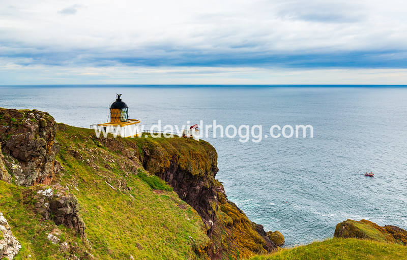 St. Abb's Head on the East Coast of Scotland.  This is a notorious coastline and the role of lighthouses and their foghorns remains important.  I like the contrast between the imposing lighthouse and its broadcasting position across the sea, versus the tiny boat lying vulnerable amidst a wide seascape.  This is accentuated by a wide angle perspective and the height of the coastal path from where this was taken.
