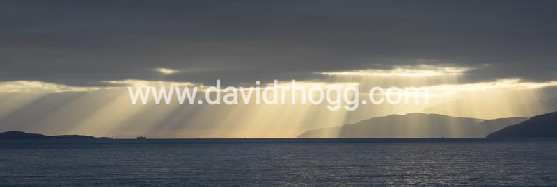 Portavadie Ferry, with sunburst and Arran hills in the background
