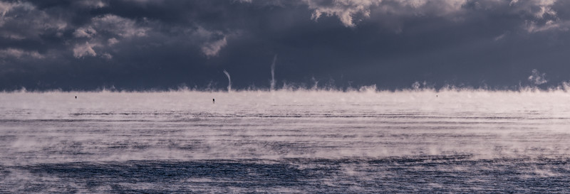 Plumes of early morning sea smoke rise in front of a fog bank several miles off shore from Portland Head Lighthouse in Cape Elizabeth, Maine.