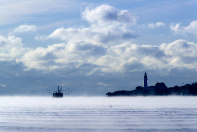 A fishing boat, surrounded by gulls and sea smoke, heads out to sea passing by Portland Head Lighthouse in Cape Elizabeth, Maine.