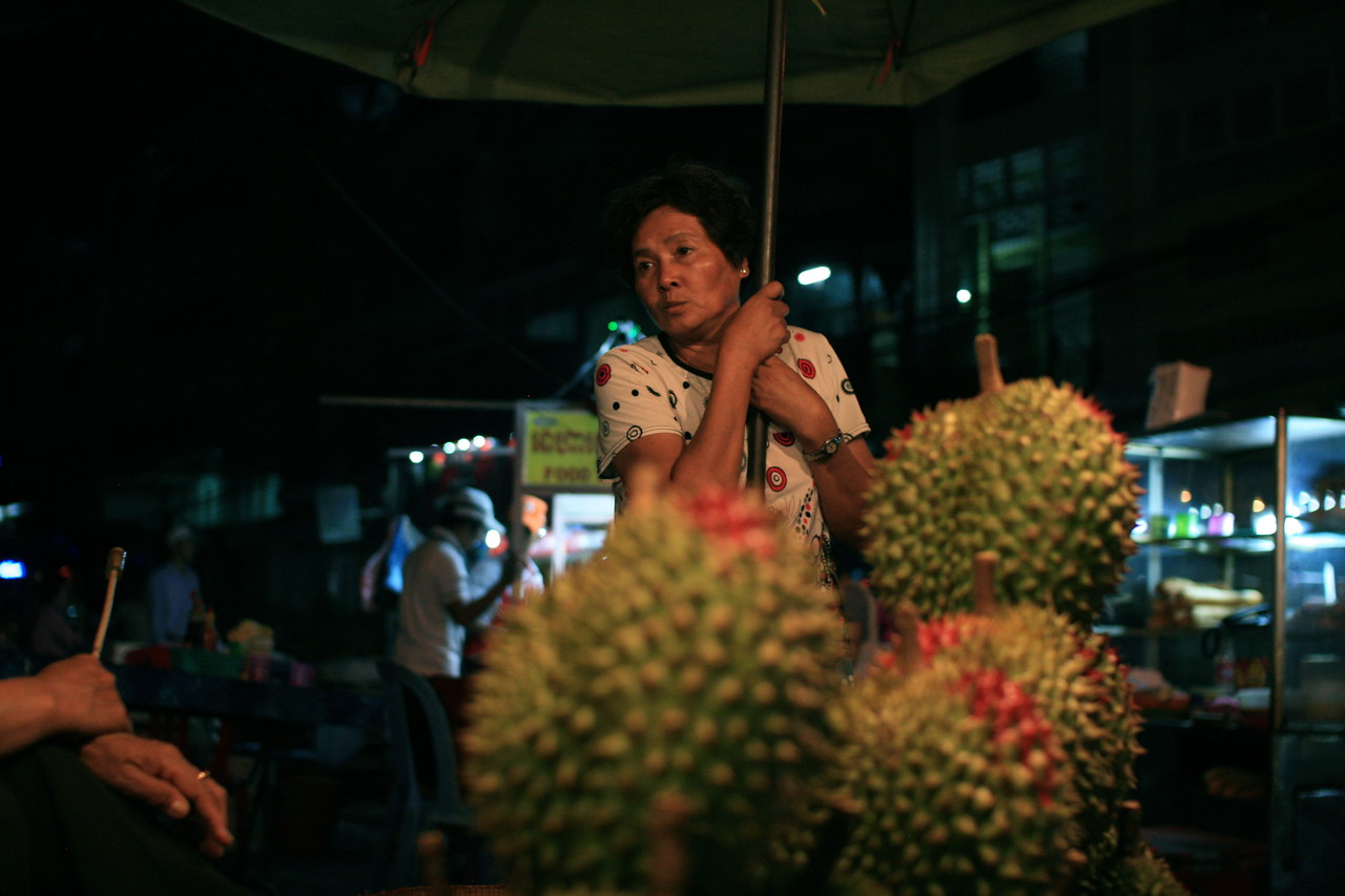 A man in Phnom Penh, Cambodia waits for someone to buy some of his jackfruits