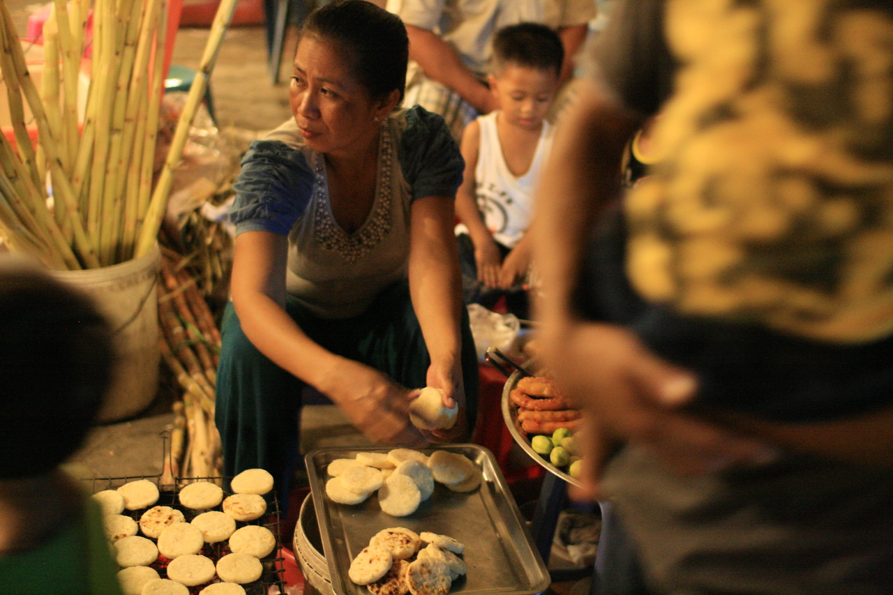 A woman at the night market in Phnom Penh, Cambodia looks up from her work.