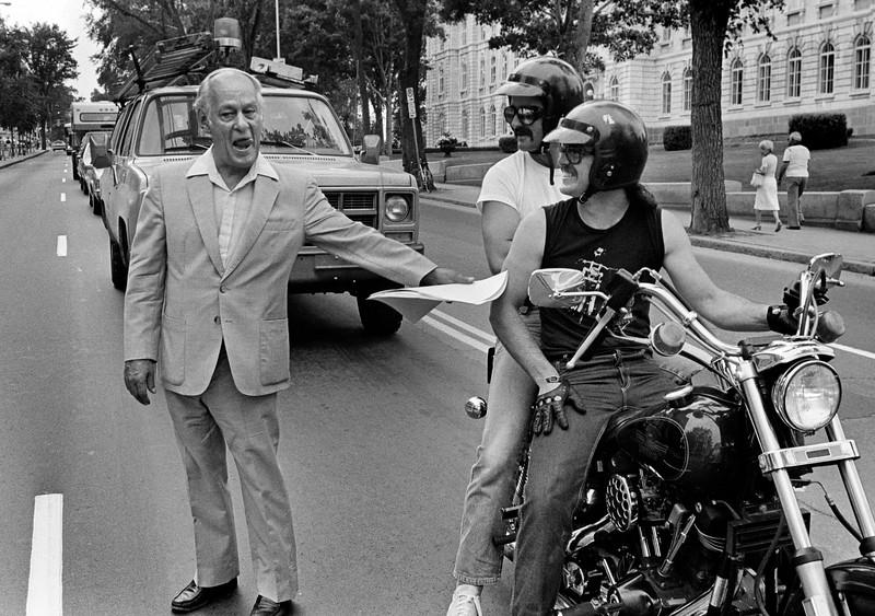René Lévesque traverse la rue en saluant 2 motards