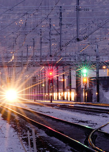 Night image of passing train and railway rails with signal lights