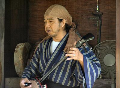 A musician playing a sanshin.