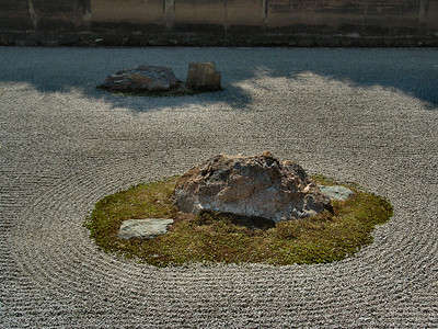 """The temple garden... is thought to date from the mid-15th century. A rock and gravel garden comprising 15 rocks in five groupings, arranged on a bed of white gravel, it is renowned throughout the world as the ultimate example of the karesansui or ""dry landscape"" style rock garden, in which nature is compressed and given abstract expression within the confines of a very narrow space."" -- from the inscription outside the temple."