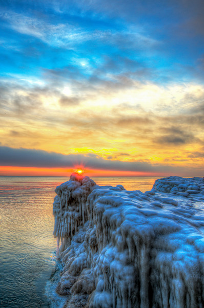 Sunrise via HDR on Lake Michigan North of Chicago 1-12-14. This was after a brief rain the night before which certainly reshaped the ice formations. It was 35°F on the 12th of January which made shooting a little easier based on it not actually being freezing. Lake Michigan is a great place and from north of Chicago you can always catch a great sunrise.
