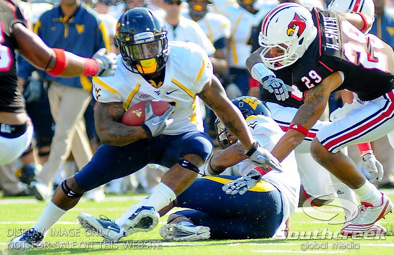 West Virginia Mountaineers wide receiver Jock Sanders (9) eludes Louisville Cardinals safety Hakeem Smith (29) during the game.  West Virginia Mountaineers leads Louisville Cardinals 14 -10 at the half PaPa Johns Cardinal Stadium Louisville, Kentucky.
