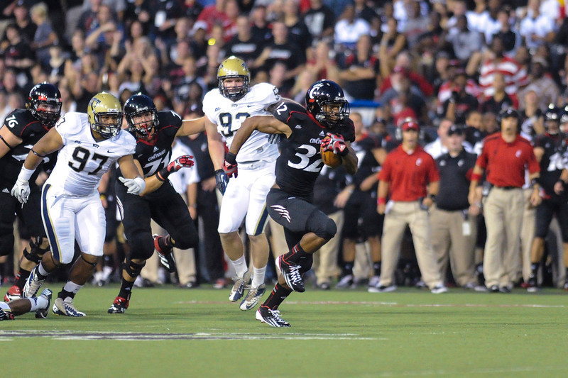 Cincinnati Bearcats running back George Winn (32) breaks away for a 58 yard touchdown on the first play of the game for the Cincinnati Bearcats.  Cincinnati Bearcats lead the Pittsburgh Panthers 17-0 at halftime at Nippert Stadium in Cincinnati, Ohio.