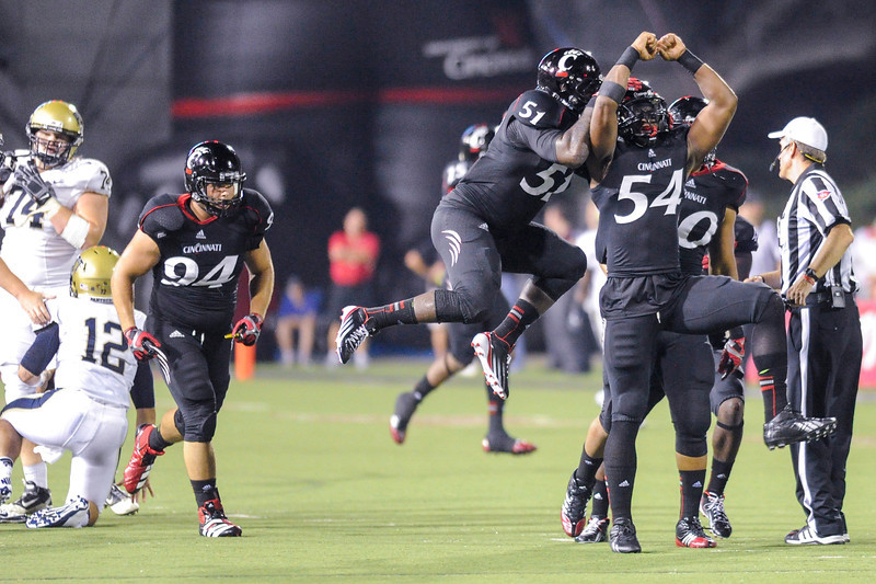 Cincinnati Bearcats defensive lineman Walter Stewart (54) celebrates with Cincinnati Bearcats linebacker Greg Blair (51) after sacking Pittsburgh Panthers quarterback Tino Sunseri (12). Cincinnati Bearcats defeated Pittsburgh Panthers 34-10 at Nippert Stadium in Cincinnati, Ohio.