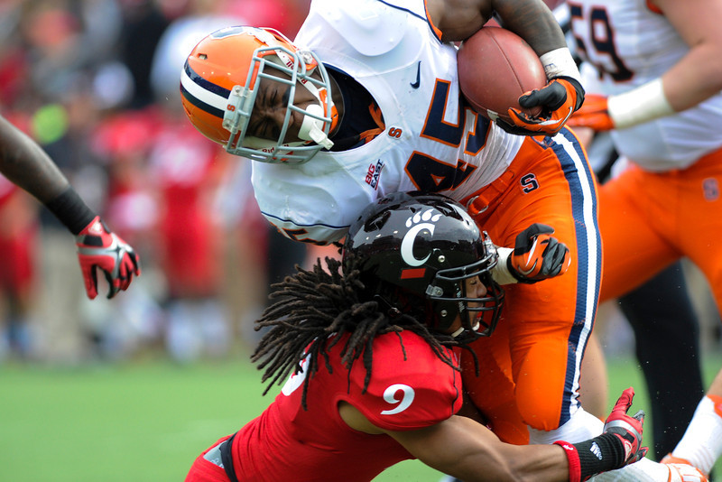 Syracuse Orange running back Jerome Smith (45) gets tackled by Cincinnati Bearcats defensive back Dominique Battle (9) during the game.  Syracuse Orange lead Cincinnati Bearcats (17-14) at the half at Nippert Stadium in Cincinnati, Ohio.