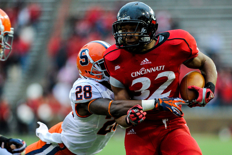 Cincinnati Bearcats running back George Winn (32) is stopped by Syracuse Orange safety Jeremi Wilkes (28).  Cincinnati Bearcats defeated Syracuse Orange (35-24) at Nippert Stadium in Cincinnati, Ohio.