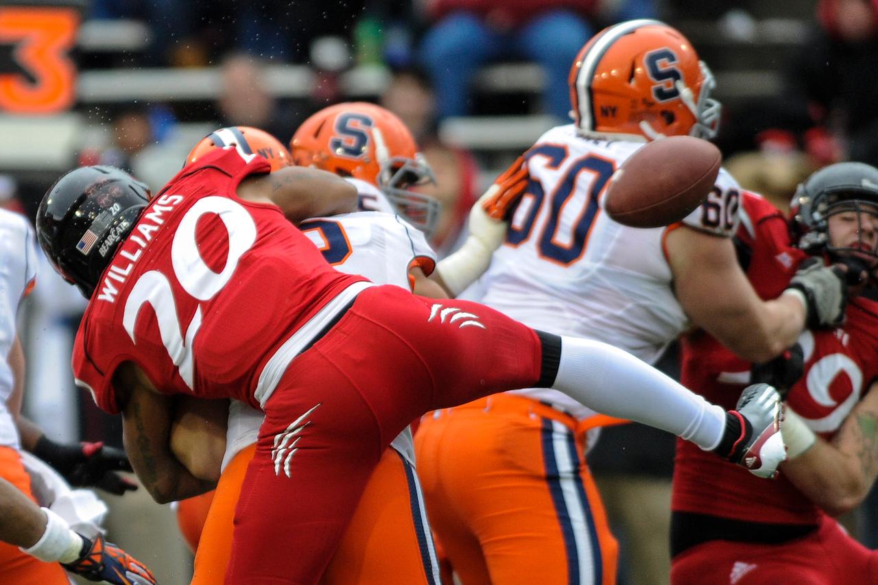 Syracuse Orange quarterback Ryan Nassib (12) looses the ball as Cincinnati Bearcats defensive back Chris Williams (20) sacks him from behind.  Cincinnati Bearcats defeated Syracuse Orange (35-24) at Nippert Stadium in Cincinnati, Ohio.