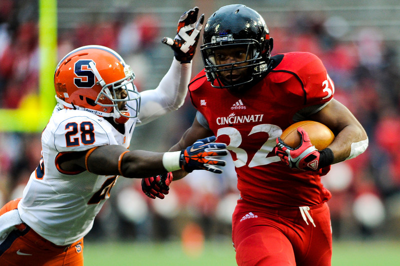 Cincinnati Bearcats running back George Winn (32) gets past Syracuse Orange safety Jeremi Wilkes (28) during the game.  Cincinnati Bearcats defeated Syracuse Orange (35-24) at Nippert Stadium in Cincinnati, Ohio.