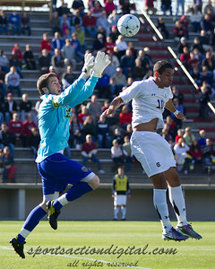 Michigan goalkeeper Chris Blais saves the ball over Carolina player Bradlee Baldez (10)