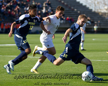 Brian Klemczak (15) kicks the ball as he is being pursued by Sam Arthur (9) and Jeffrey Quijano (12)
