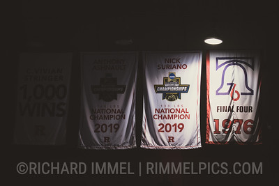 NCAA champion banners for Nick Suriano and Anthony Ashnault hanging from the rafters at the Rutgers Athletic Center.
