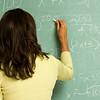 Female student writing on blackboard