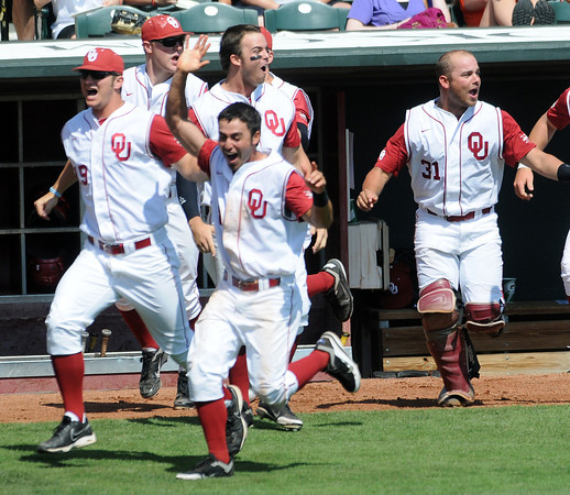 Oklahoma players rush to the plate to congratulate teammate Garrett Carey  Wednesday, May 22, 2012, after his walk-off homerun defeated Oklahoma State in the opening round of the Big 12 championship at the Chickasaw Bricktown Ballpark. Jerry Laizure/The Transcript
