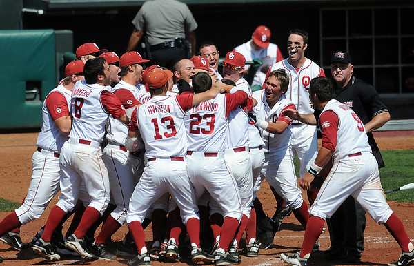 """Oklahoma players mob teammate Garrett Carey Wednesday, May 22, 2012, after his walk-off homerun defeated Oklahoma State in the opening round of the Big 12 championship at the Chickasaw Bricktown Ballpark. Additional photos can be viewed here <a href=""""http://photos.NormanTranscript.com/CollegeSports"""">http://photos.NormanTranscript.com/CollegeSports</a> Jerry Laizure/The Transcript"""