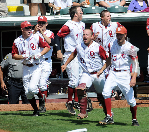 """Oklahoma players rush to the plate to congratulate teammate Garrett Carey  Wednesday, May 22, 2012, after his walk-off homerun defeated Oklahoma State in the opening round of the Big 12 championship at the Chickasaw Bricktown Ballpark. Additional photos can be viewed here <a href=""""http://photos.NormanTranscript.com/College"""">http://photos.NormanTranscript.com/College</a> Sports Jerry Laizure/The Transcript"""