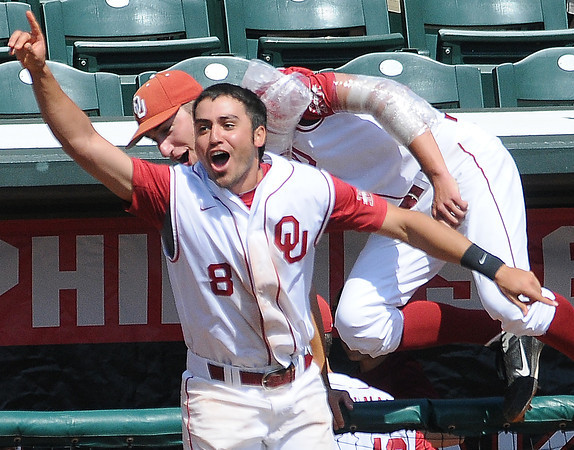 """Oklahoma players Jack Mayfield (8) and Dillon Overton rush to congratulate teammate Garrett Carey  Wednesday, May 22, 2012, in the opening round of the Big 12 championship at the Chickasaw Bricktown Ballpark. Carey's walk-off homerun gave the Sooners a 1-0 win over Oklahoma State. Additional photos can be viewed here <a href=""""http://photos.NormanTranscript.com/College"""">http://photos.NormanTranscript.com/College</a> Sports Jerry Laizure/The Transcript"""