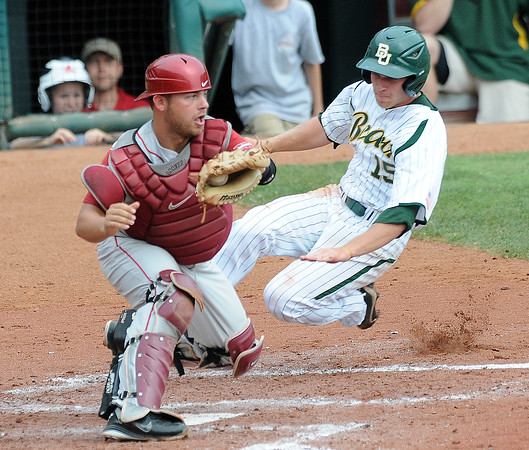 Oklahoma catcher Tanner Toal catches the ball while Baylor runner Adam Toth slides home Saturday, May 26, 2012, in the Big 12 baseball championship at the Chickasaw Bricktown Ballpark in Oklahoma City. Toth was out on the play.  Jerry Laizure/The Transcript
