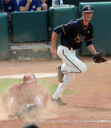 MIssouri reliever Blake Holavach celebrates while Oklahoma pinch runner Dustin Dishman slides into home Sunday, May 27, 2012, in the title game of the Big 12 baseball championship at the Chickasaw Bricktown Ballpark in Oklahoma City. Dishman did not score as Chase Simpson's single hit Caleb Bushyhead on the foot and Bushyhead was called out for interference.  Jerry Laizure/The Transcript