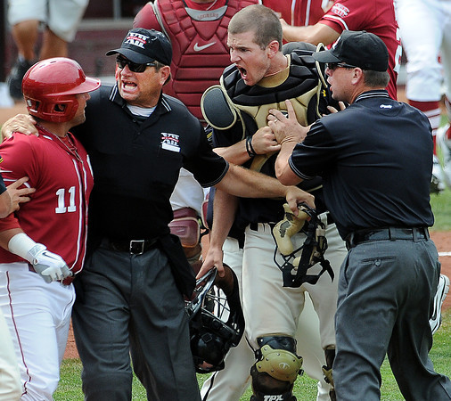 Umpires Jeff Henrichs (left) and Chris Coskey separate Oklahoma outfielder Cody Reine (11) and MIssouri catcher Ben Turner Sunday, May 27, 2012, after Reine was hit by a pitch in the title game of the Big 12 baseball championship at the Chickasaw Bricktown Ballpark in Oklahoma City. Jerry Laizure/The Transcript