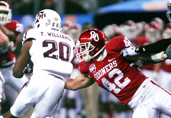 Oklahoma's Jessie Paulson (42) tries to pull down Texas A&M's Trey Williams as he runs with the ball during the Sooners' game against the Aggies at Cowboy Stadium in Dallas.<br /> Kyle Phillips/The Transcript