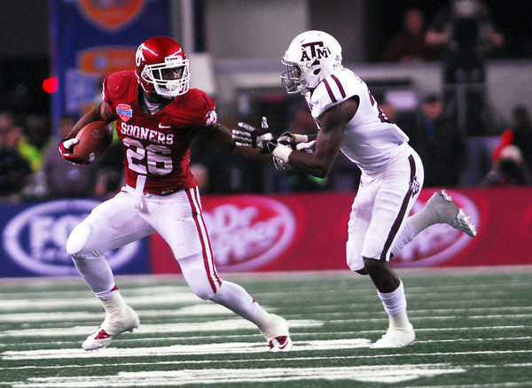 OU running back Damian Williams pushes away a Texas A&M player as he runs with the ball during the Sooners' game against the Aggies at Cowboy Stadium in Dallas.<br /> Kyle Phillips/The Transcript