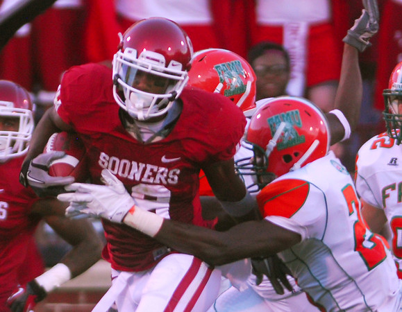 OU wide receiver Justin Brown (19) tries to push his way through Florida A&M defenders as he runs with the ball during the Sooners' game against the Rattlers Saturday at Owen Field.<br /> Kyle Phillips/The Transcript