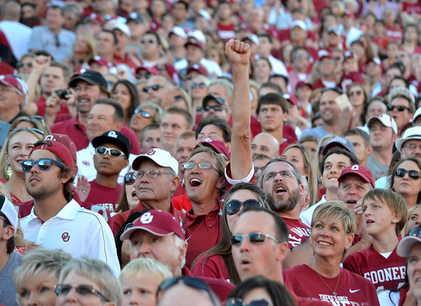 An OU fan cheers from the stands as the Sooners prepare to take the field Saturday before their game with Florida A&M at Owen Field.<br /> Kyle Phillips/The Transcript