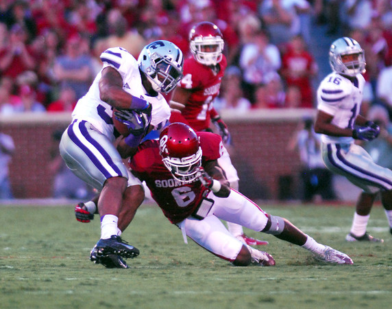 OU V K-State1<br /> Oklahoma's Demontre Hurst (6) brings down a Kansas State player as he runs with the ball Saturday during the Sooners' game against the Wildcats at Owen Field.<br /> Kyle Phillips/The Transcript