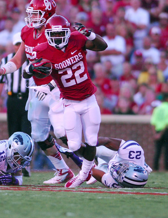 OU running back Roy Finch (22) tries to slip past the Kansas State defense as he runs with the ball Saturday during the Sooners' game against the Wildcats at Owen Field.<br /> Kyle Phillips/The Transcript