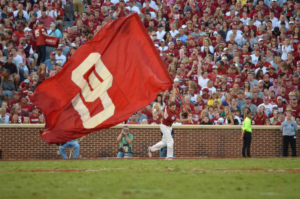 A member of the Ruf/Neks runs on the filed with an OU flag after the Sooners score their first touchdown against Kansas State Saturday at Owen Field.<br /> Kyle Phillips/The Transcript