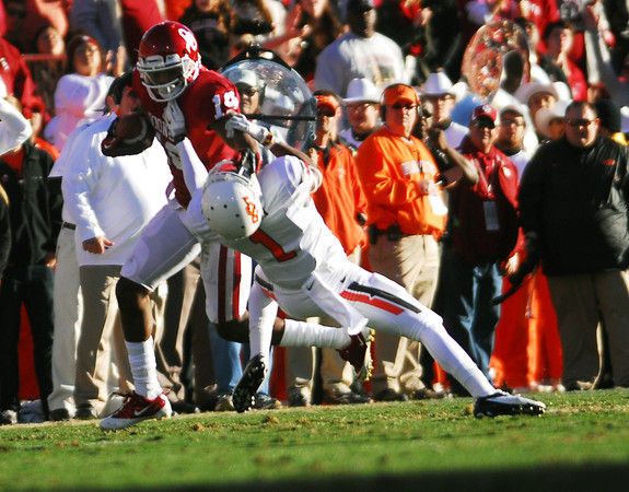 OU receiver Justin Brown (19)  pushes away an OSU player as he runs with the ball Saturday during the Sooners' game against the Cowboys at Owen Field.<br /> Kyle Phillips/The Transcript