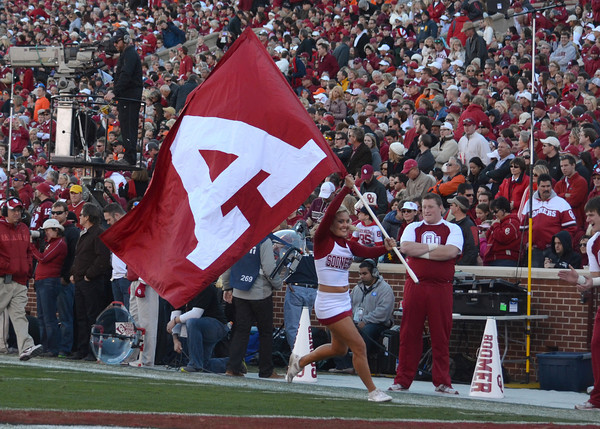 An Oklahoma cheerleader carries a part of the OU flag through the end zone Saturday after the Sooners score a touchdown against OSU.<br /> Kyle Phillips/The Transcript
