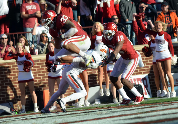 OU's Trey Millard (33) leaps over an OSU player, scoring a touchdown Saturday during the Sooners' game against the Cowboys at Owen Field.<br /> Kyle Phillips/The Transcript