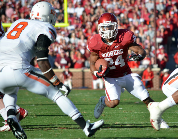 OU running back Brennan Clay (24) looks for a way to get around OSU's Daytawion Lowe (8)  on a run play Saturday during the Sooners' game against the Cowboys at Owen Field.<br /> Kyle Phillips/The Transcript