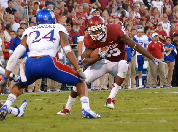OU receiver Justin Brown (19) jukes to get around Kansas defender Bradley McDougal (24) Saturday during the Sooners' game against the Jayhawks.<br /> Kyle Phillips/The Transcript