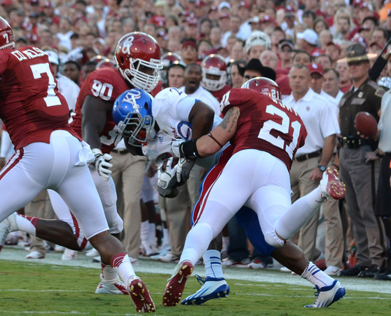 OU's David King (90) and Tom Wort (21) bring down a Kansas player as he runs with the ball during the Sooners' game against the Jay Hawks at Owen Field.<br /> Kyle Phillips/The Transcript