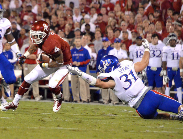 OU receiver Kenny Stills (4) tries to get around Kansas defender Ben Heeney (31) during the Sooners' game against the Jay Hawks at Owen Field.<br /> Kyle Phillips/The Transcript