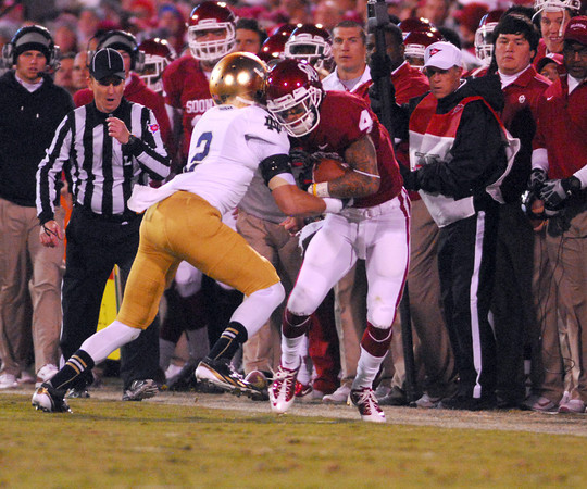 OU receiver Kenny Stills (4) gets pushed out of bounds by a Notre Dame defender Saturday during the Sooners' game against the Fighting Irish at Owen Field.<br /> Kyle Phillips/The Transcript