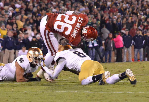 OU running back Damien Williams (26) gets tackled by Notre Dame's Kendall Moore (8) as he runs with the ball during the Sooners' game against the Fighting Irish at Owen Field.<br /> Kyle Phillips/The Transcript