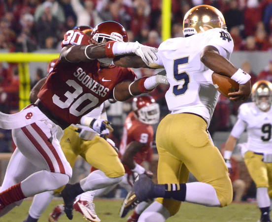 OU's Javon Harris (30) pulls down Notre Dame quarterback Everett Golson (5) as he runs with the ball during the Sooners' game against the Fighting Irish Saturday at Owen Field.<br /> Kyle Phillips/The Transcript