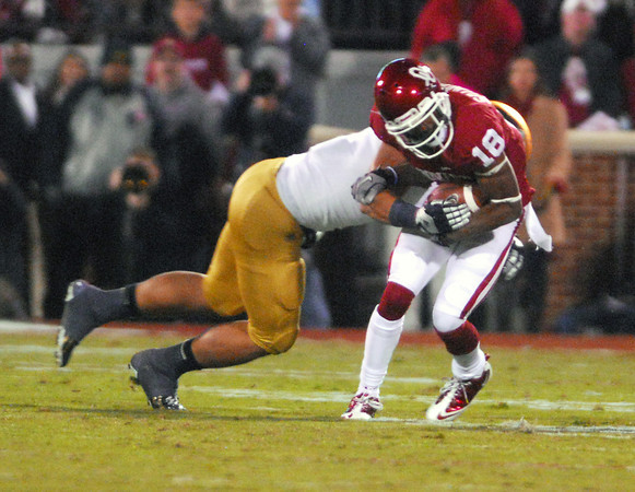 OU receiver Jalen Saunders (18) gets tackled by a Notre Dame player after he catches a pass Saturday during the Sooners' game against the Fighting Irish at Owen Field.<br /> Kyle Phillips/The Transcript