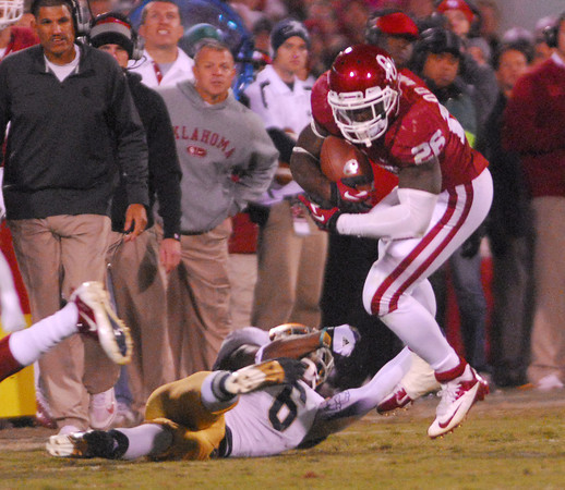 OU running back Damien Williams (26) gets tripped up by Notre Dame's KeiVarae Russell (6) as he runs with the ball Saturday during the Sooners' game against the Fighting Irish.<br /> Kyle Phillips/The Transcript