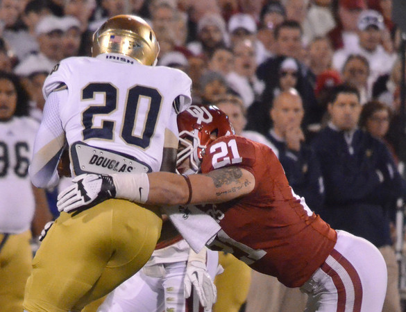 OU's Tom Wort (21) pulls down Notre Dame running back Cierre Wood (20) as he runs with the ball during the Sooners' game against the Fighting Irish Saturday at Owen Field.<br /> Kyle Phillips/The Transcript